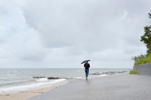 Poland, Niechorze, Woman under black umbrella walking on beachの写真素材 [FYI02204843]