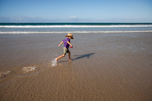 Australia, Queensland, Sunshine Coast, Coolum, Boy (4-5) running through water on beachの写真素材 [FYI02204865]