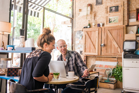 Israel, Tel Aviv, Man and woman sitting in cafe and looking at phoneの写真素材 [FYI02204880]