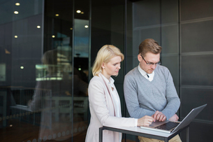 Finland, Two colleagues using laptopの写真素材 [FYI02204882]