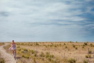 Sweden, Oland, Byxelkrok, Woman cycling across  fieldの写真素材 [FYI02204886]