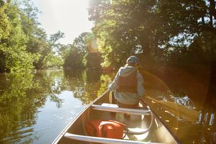 Sweden, Vastergotland, Lerum, Savean, Boy (12-13) in baseball cap sitting in canoeの写真素材 [FYI02204897]