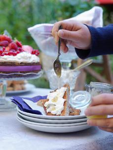 Sweden, Woman pouring honey on dessertの写真素材 [FYI02204903]