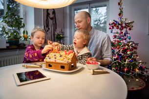 Sweden, Man and two boys (18-23 months, 4-5) decorating gingerbread houseの写真素材 [FYI02204912]
