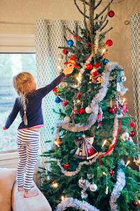 Finland, Girl (4-5) decorating christmas treeの写真素材 [FYI02204914]