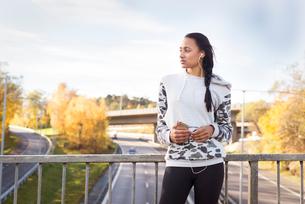Sweden, Vastergotland, Gothenburg, Young woman listening to music on smart phoneの写真素材 [FYI02204917]