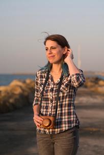 Israel, Tel Aviv, Woman in plaid shirt with analog cameraの写真素材 [FYI02204920]
