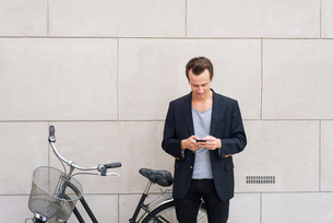 Sweden, Man with mobile phone standing next to his bikeの写真素材 [FYI02204927]