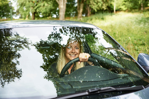 Sweden, Uppland, Smiling woman travelling by car in countrysideの写真素材 [FYI02204931]