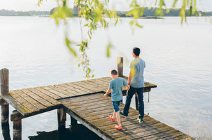 Sweden, Blekinge, Karlskrona, Father and son (8-9) by lakeの写真素材 [FYI02204937]