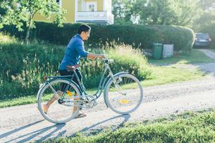 Sweden, Smaland, Mortfors, Man pushing bicycle on roadの写真素材 [FYI02204938]