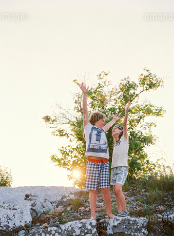 Sweden, Two boys (8-9, 10-11) standing on rock with hands upの写真素材 [FYI02204941]