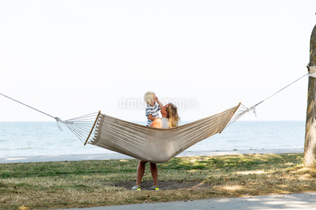 Sweden, Gotland, Mid adult woman and boy (2-3) in hammock at seashoreの写真素材 [FYI02204988]