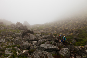 Norway, Lofoten, Moskenesoya, Tourists hiking in fogの写真素材 [FYI02204990]