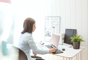 Sweden, Young woman working on laptop in officeの写真素材 [FYI02205053]
