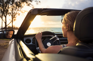 USA, Hawaii, Oahu, Woman in car by beach at sunsetの写真素材 [FYI02205068]