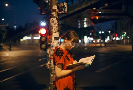 Germany, Berlin, Beautiful woman reading in city at nightの写真素材 [FYI02205071]