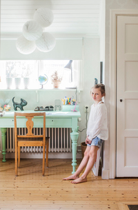 Sweden, Girl (8-9) leaning on wall in roomの写真素材 [FYI02205083]
