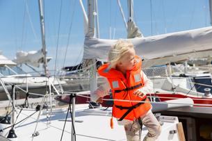 Sweden, Sodermanland, Trosa, Boy (2-3) with windswept hair on yachtの写真素材 [FYI02205091]