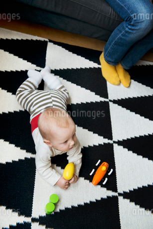 Sweden, Little baby boy (6-11 months) lying on carpet and playing with toysの写真素材 [FYI02205104]
