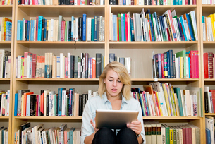 Sweden, Young woman sitting by bookshelves and using digital tabletの写真素材 [FYI02205149]