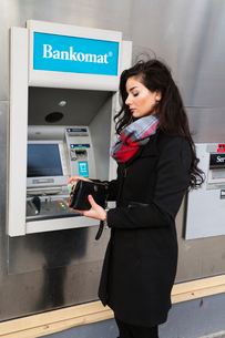 Sweden, Stockholm, Woman taking money from ATMの写真素材 [FYI02205151]