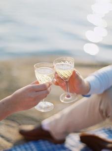 Sweden, Bohuslan, Fjallbacka, Couple toasting with glasses of champagne on sandy beachの写真素材 [FYI02205166]
