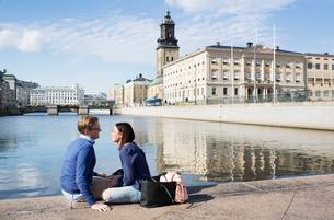 Sweden, Vastergotland, Gothenburg, Smiling couple sitting on promenade by canalの写真素材 [FYI02205170]