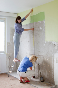 Finland, Young women measuring wall for renovationの写真素材 [FYI02205183]