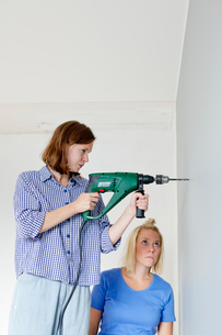 Finland, Young woman drilling in wallの写真素材 [FYI02205195]