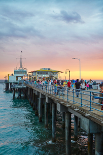 USA, California, Los Angeles, Santa Monica Pier, People walking on pier at sunsetの写真素材 [FYI02205203]