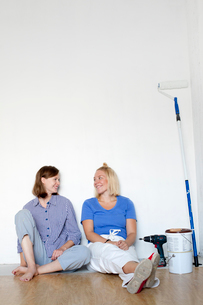 Finland, Young women resting by wall after home renovation workの写真素材 [FYI02205213]