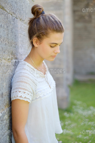 Sweden, Ostergotland, Portrait of teenage girl (14-15) leaning against wall outdoorsの写真素材 [FYI02205225]