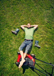 Finland, Man lying on grass with feet up on lawn mover in summerの写真素材 [FYI02205226]