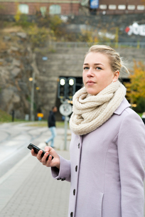 Sweden, Vastra Gotaland, Gothenburg, Thoughtful young woman in street with smart phone in handの写真素材 [FYI02205235]