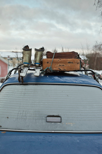 Sweden, Blue car with suitcase and ski-boots on topの写真素材 [FYI02205237]