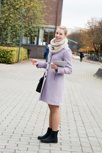 Sweden, Vastra Gotaland, Gothenburg, Smiling young woman in overcoat standing on sidewalk with digitの写真素材 [FYI02205243]
