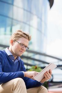 Sweden, Vastergotland, Gothenburg, Young man sitting against glass building and using digital tabletの写真素材 [FYI02205248]
