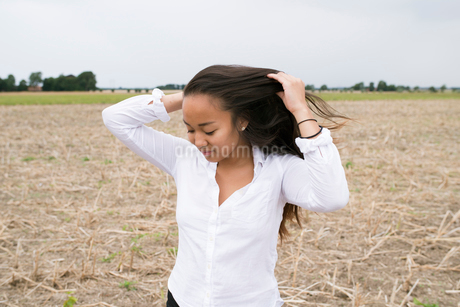 Sweden, Skane, Jakriborg, Portrait of young woman with brown hair in fieldの写真素材 [FYI02205256]