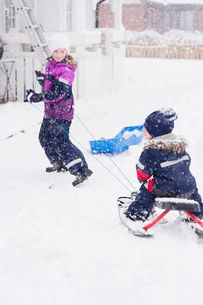 Sweden, Vastmanland, Girl (10-11) pulling brother (2-3) on sledの写真素材 [FYI02205260]