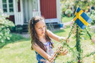 Sweden, Smaland, Mortfors, Girl (10-11) decorating swedish flagの写真素材 [FYI02205285]