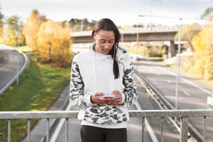 Sweden, Vastergotland, Gothenburg, Young woman listening to music on smart phoneの写真素材 [FYI02205293]