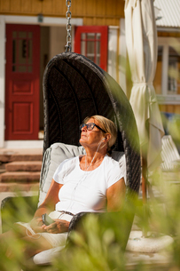 Sweden, Senior woman sitting in hooded beach chair and listening to music on smart phoneの写真素材 [FYI02205308]