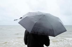 Poland, Niechorze, Woman under black umbrella watching Baltic Seaの写真素材 [FYI02205310]