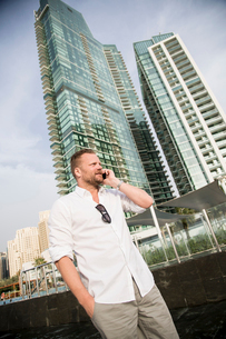 United Arab Emirates, Dubai, Mature man talking on telephone with skyscrapers in backgroundの写真素材 [FYI02205321]