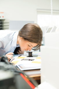 Sweden, Young woman looking at printouts through magnifying glassの写真素材 [FYI02205334]