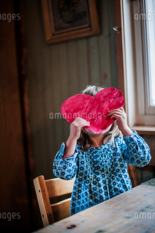 Sweden, Girl (2-3) holding paper heart in front of faceの写真素材 [FYI02205342]