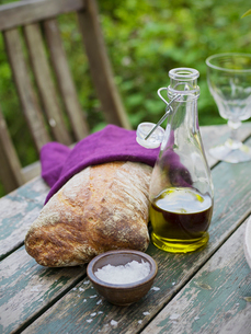 Sweden, Bread, olive oil in carafe and small bowl with salt on tableの写真素材 [FYI02205344]