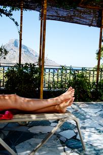 Greece, Kalymnos, Woman´s legs on sun loungerの写真素材 [FYI02205370]