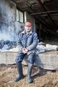 Sweden, Uppland, Grillby, Senior farmer sitting in front of barnの写真素材 [FYI02205388]